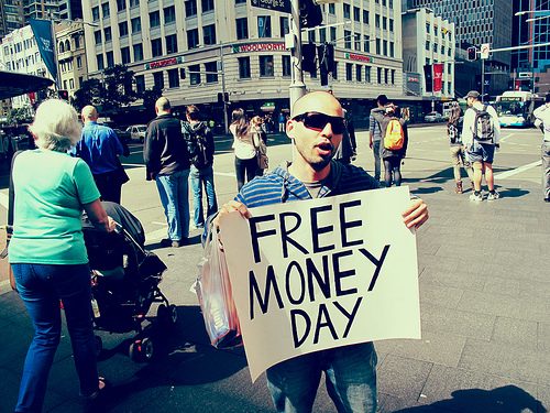 Guy holds up Free Money Day sign in Sydney's central business district
